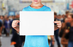 Unidentified girl holds a blank sheet of paper Stock Images