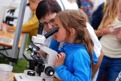 An Unidentified Girl Looks through the Microscope Royalty Free Stock Photos