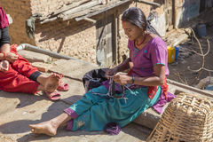 An unidentified girl sews a dress in the backyard on December 2, Stock Photo