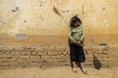 An unidentified girl standing near wall of school compound Royalty Free Stock Images