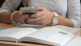 Unknown girl student with smartphone. Unidentified girl student with beautiful manicure in white lace shirt and with accessories on hands sit at wooden desk with stock footage