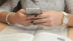 Unknown girl student with smartphone. Unidentified girl student with beautiful manicure in white lace shirt and with accessories on hands sit at wooden desk with stock video