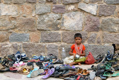 An unidentified girl watches foot wear of hindu devotees Royalty Free Stock Photography