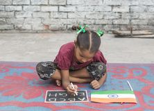 A girl studying elementary education in open school. Unidentified girl writing alphabet in a chalkboard and showing in ludhiana, punjab, india on 15 august 2017 stock images