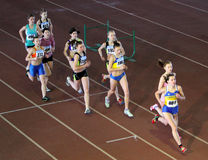 Unidentified girls run 2,000 m. steeplechase race Royalty Free Stock Images