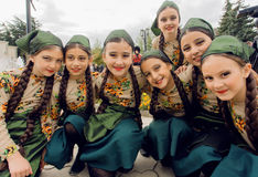 Unidentified girls in traditional Georgian costumes posing in crowd of the party stock image