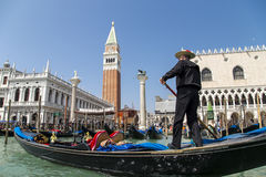 Unidentified gondolier wearing traditional dress in the gondola and sail on a Venetian canal Royalty Free Stock Images