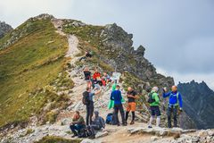 Unidentified group of hikers resting and exhausted at Krzyzne Pass in High Tatra Mountai Stock Photos