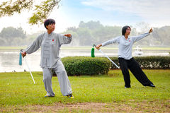 Unidentified group of people practice Chinese sword with Tai Chi Chuan in a park. BANGKOK, THAILAND - FEBRUARY 20, 2016: Unidentified group of people practice Royalty Free Stock Photo