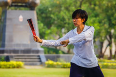 Unidentified group of people practice Tai Chi Chuan in a park. BANGKOK, THAILAND - FEBRUARY 20, 2016: Unidentified group of people practice Tai Chi Chuan in a Stock Photos