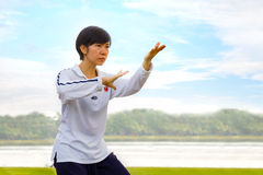 Unidentified group of people practice Tai Chi Chuan in a park. BANGKOK, THAILAND - FEBRUARY 20, 2016: Unidentified group of people practice Tai Chi Chuan in a Royalty Free Stock Photos