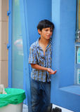 An unidentified gypsy boy beg for money from a passerby in Craiova Royalty Free Stock Photos