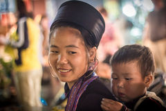 Unidentified Hmong Girl Carrying Baby in Sapa, Lao Cai,Vietnam. Unidentified Hmong girl carrying baby and wearing traditional attire in Sapa town, Lao Cai Stock Images