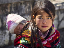 Unidentified Hmong Girl Carrying Baby in Sapa, Vietnam Stock Photo