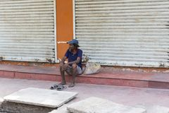 An unidentified homeless man sleeps on the road street. Poor Indians for charity. PONDICHERY, PUDUCHERRY, TAMIL NADU, INDIA - SEPTEMBER CIRCA, 21017. An royalty free stock photography
