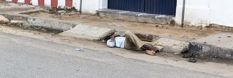 An unidentified homeless man sleeps on the road street. Poor Indians for charity. PONDICHERY, PUDUCHERRY, TAMIL NADU, INDIA - SEPTEMBER CIRCA, 21017. An royalty free stock image