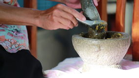 Unidentified human hand pounding spices in stone mortar, traditional Thai curry.  stock video footage