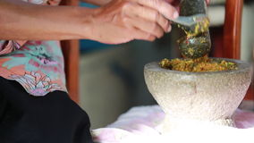 Unidentified human hand pounding spices in stone mortar, traditional Thai curry.  stock video