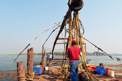 Unidentified Indian fishermen descend their Chinese fishing net into the sea Stock Photography
