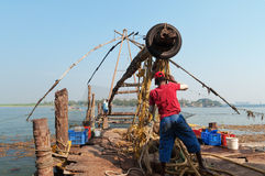 Unidentified Indian fishermen descend their Chinese fishing net into the sea Royalty Free Stock Image