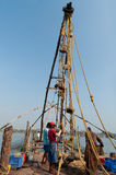 Unidentified Indian fishermen descend their Chinese fishing net into the sea Stock Photo