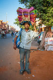 Unidentified Indian man carries colorful blankets Stock Photos
