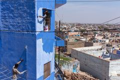 Unidentified indian men painting house in blue color into the Blue City Jodhpur, India. Stock Image