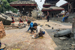 Unidentified kids feeding pigeons with dry corn at Durbar Square in Bhaktapur, Kathmandu, Nepal, after major earthquake in 2015. Stock Photos