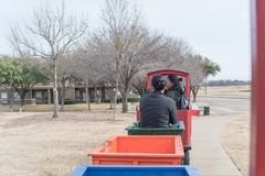 Kid trackless train ride in public winter event in Irving, Texas. Unidentified kids and parents riding on trackless train ride wagon near local street. Train Stock Photo