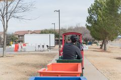 Kid trackless train ride in public winter event in Irving, Texas. Unidentified kids and parents riding on trackless train ride wagon near local street. Train Stock Image