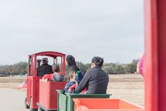 Kid trackless train ride in public winter event in Irving, Texas. Unidentified kids and parents riding on trackless train ride wagon. Public park winter event in Stock Photography