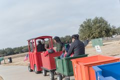 Kid trackless train ride in public winter event in Irving, Texas. Unidentified kids and parents riding on trackless train ride wagon. Train crossing sign at Stock Photo