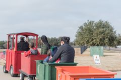 Kid trackless train ride in public winter event in Irving, Texas. Unidentified kids and parents riding on trackless train ride wagon. Train crossing sign at Stock Image