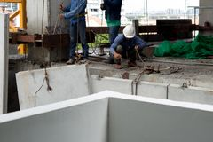 Labor man working on construction site with helmet pulling concr. Unidentified labor man working on construction site with helmet pulling concrete slabs using Royalty Free Stock Photography