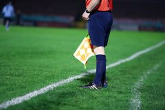 Unidentified linesman referee stands still with the flag down stock photo