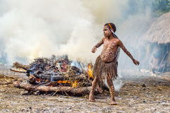 Unidentified little girl  of Dugum Dani tribe is near the fire in the smoke. Stock Photo