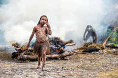 Unidentified little girl of Dugum Dani tribe is near the fire in the smoke. Stock Photography
