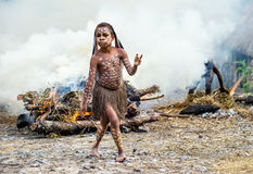 Unidentified little girl of Dugum Dani tribe is near the fire in the smoke. Stock Photos