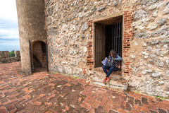 Unidentified local girl sitting in front of city fortress entrance, Santo Domingo, Dominican Republic Stock Images