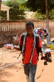 Unidentified local man carries some goods along the road in the. CANCHUNGO, GUINEA BISSAU - MAY 3, 2017: Unidentified local man carries some goods along the road royalty free stock photos
