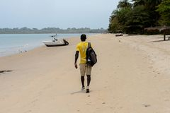 Unidentified local man in yellow shirt with backpack walks alon. RUBANE, GUINEA BISSAU - MAY 4, 2017: Unidentified local man in yellow shirt with backpack walks stock photos