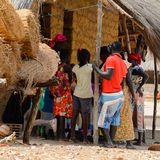 Unidentified local people gather near the shack and heap of hay. ORANGO ISLAND, GUINEA BISSAU - MAY 3, 2017: Unidentified local people gather near the shack and royalty free stock photos