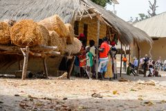 Unidentified local people gather near the shack and heap of hay. ORANGO ISLAND, GUINEA BISSAU - MAY 3, 2017: Unidentified local people gather near the shack and stock photo