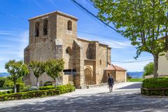 Unidentified male pilgrim passes by the Church of San Andres on the Camino de Santiago, Way of St. James in Zariquiegui, Navarre, stock photo