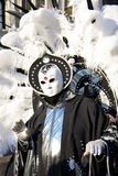 An unidentified man in black fancy dress with huge white feathers on the back wears a white mask during Venice Cernival Royalty Free Stock Image