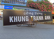 Unidentified man is carrying long signboard by tricycle in Vihn, Vietnam. Vinh, Vietnam - May 29, 2015: unidentified man is carrying long signboard by tricycle stock photos