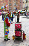 Unidentified man covered in plastic flowers to make show and earn money at Castle square Stock Photography