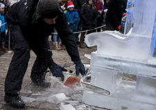 Unidentified man creating artwork out of block of ice. SZCZECIN, POLAND -  DECEMBER 6, 2014: Unidentified man with chainsaw Stihl, creating artwork out of the Royalty Free Stock Image
