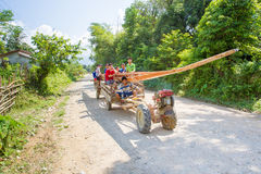 Unidentified man driving tractor on a rural road. VANG VIENG, LAOS - OCT 18: unidentified man driving tractor on a rural road on oct 18, 2015, in Vang Vieng Stock Photos