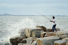 Unidentified man fishing with big wave splashing Stock Photos